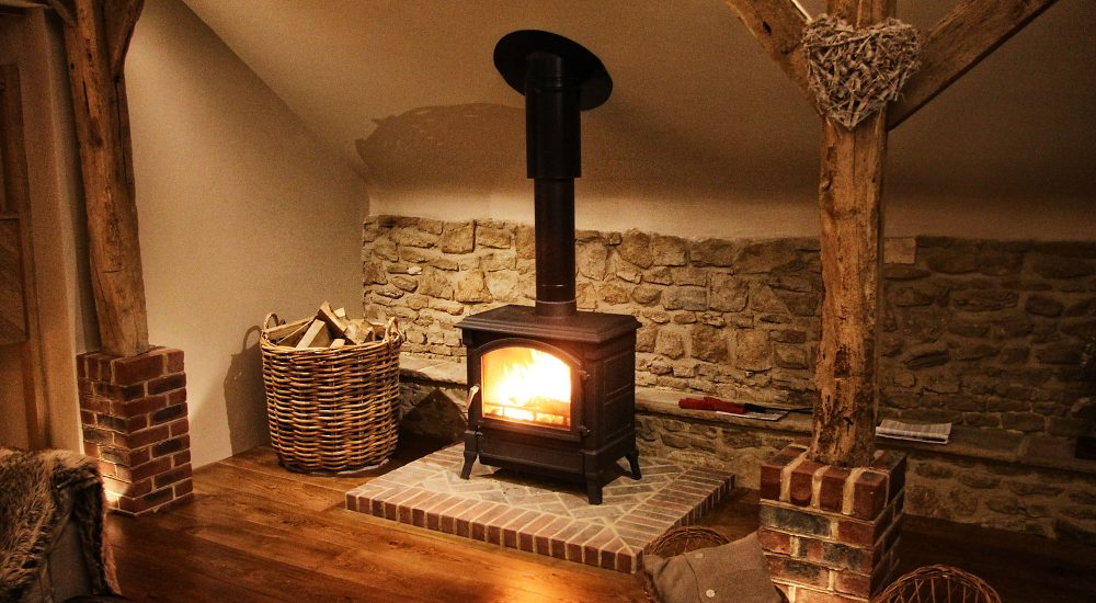 wood burning stove in rustic barn conversion, Surrey