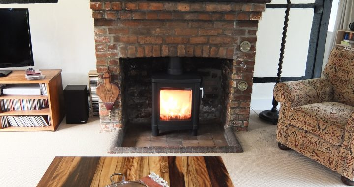 wood burning stove in brick fireplace surround