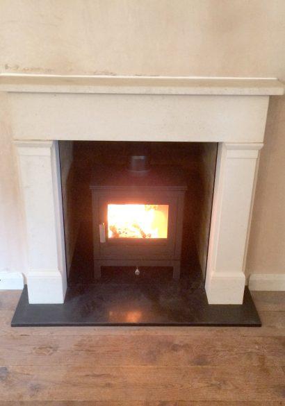 wood burning stove with limestone surround