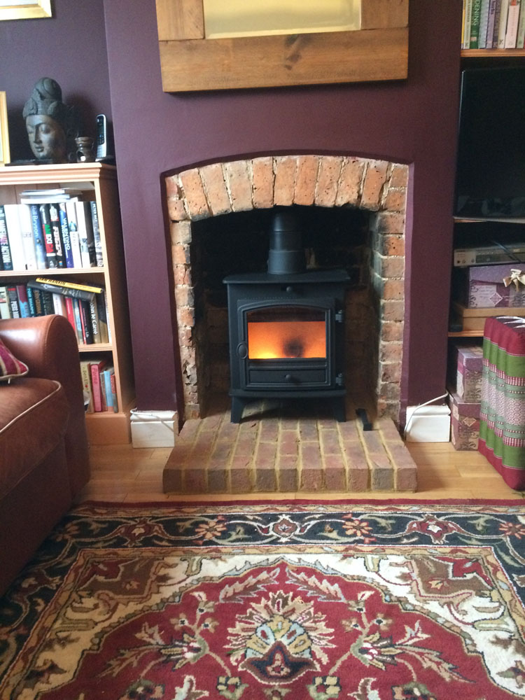 rustic brickwork fireplace with wood burning stove