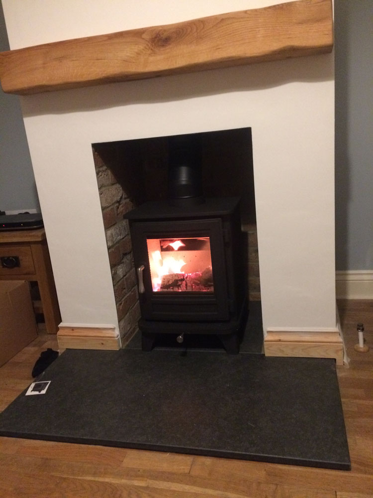 log burner in fireplace lined with brick slips