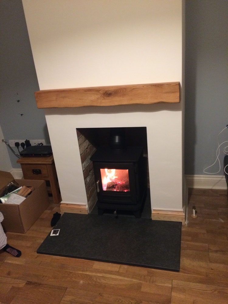 log burner with granite hearth, brick slips and oak mantlepiece