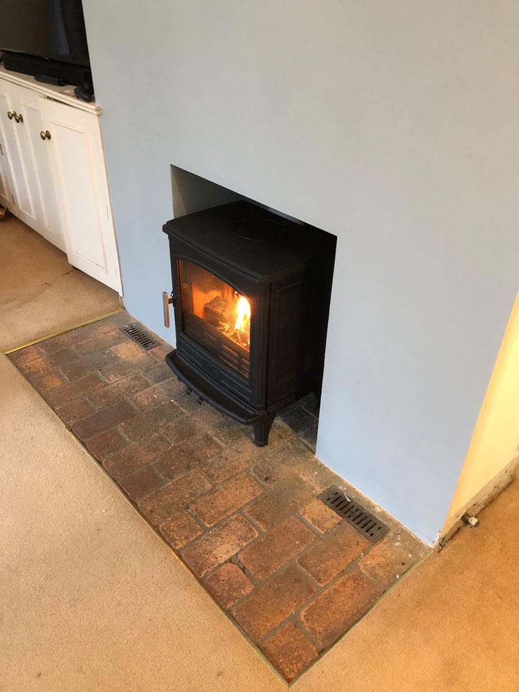 cast iron wood burner with brick hearth