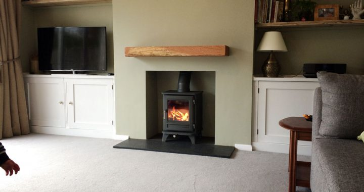 Sage green Chesney's log burner with oak mantlepiece
