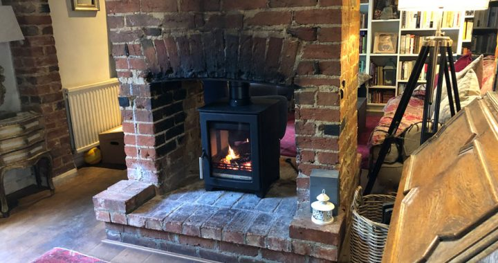 Double sided wood burner in rustic brick fireplace