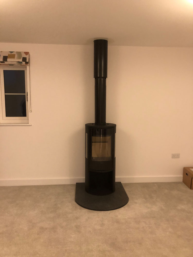 freestanding wood burner on rounded granite hearth