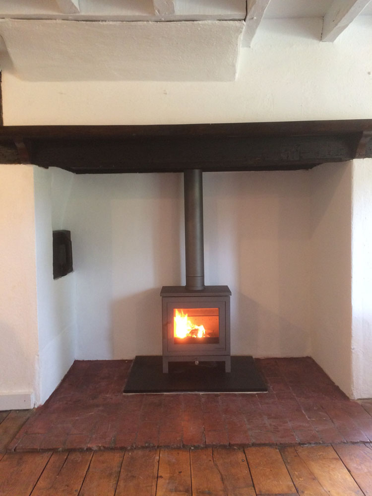 modern wood burner in inglenook fireplace