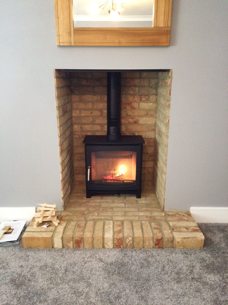 modern log burner with brick fireplace