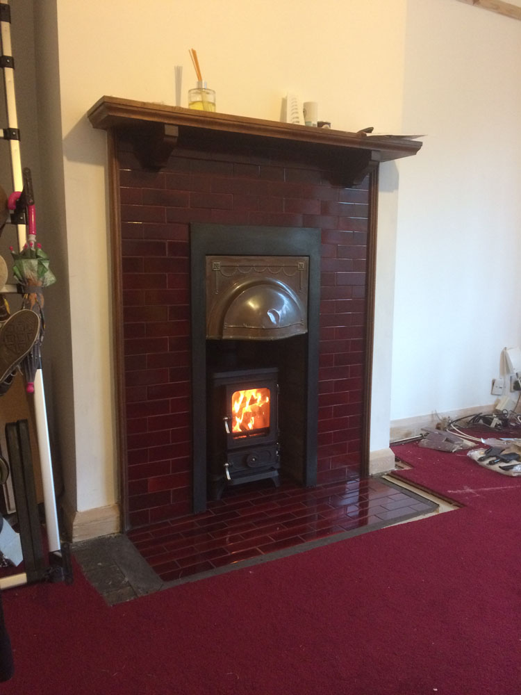 Vintage tile fireplace with hobbit log burner