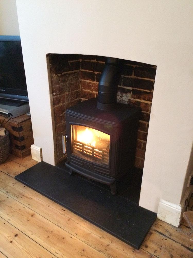cast iron wood burner in brick fireplace